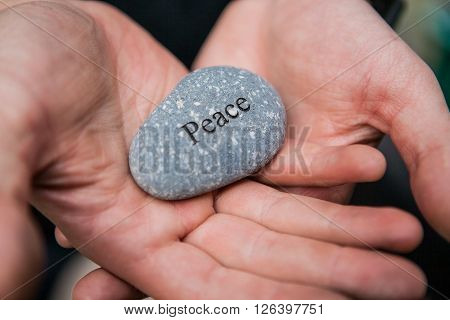 Hands holding pebble stones with the word peace