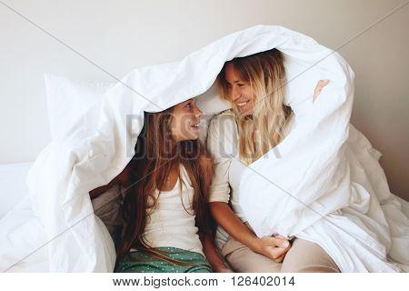 Mom with her tween daughter relaxing in bed, positive feelings, good relations.
