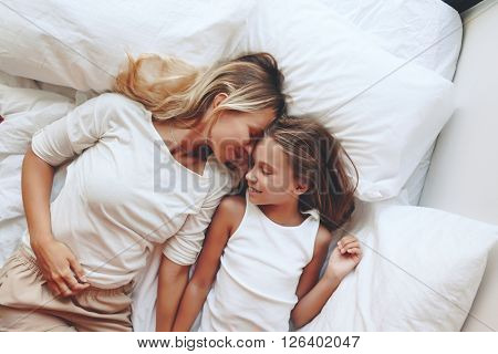 Mom with her tween daughter relaxing in bed, positive feelings, good relations. Top view.