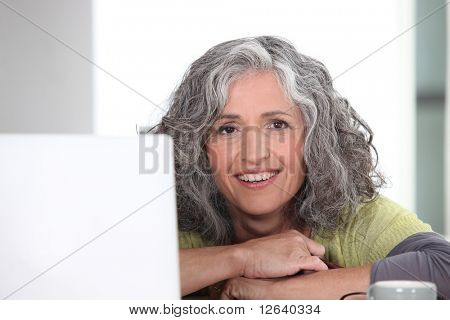 Portrait of a Senior woman smiling in front of a computer