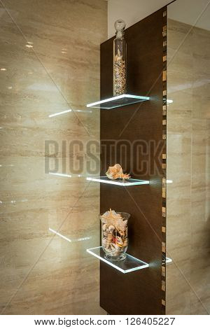 Glass shelf in bathroom with ornaments and decorations earth tones