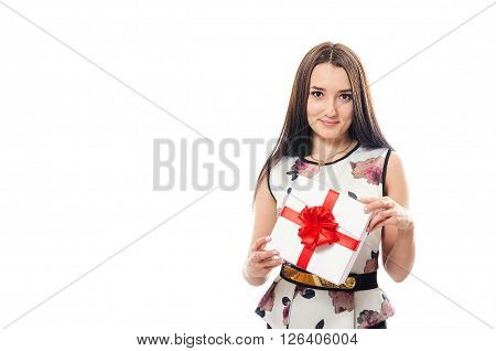 The young girl in a dress holds a box with a gift in hand and smiles. St. Valentine's Day.