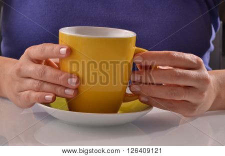 Holding yellow coffee cup. Hot coffee.