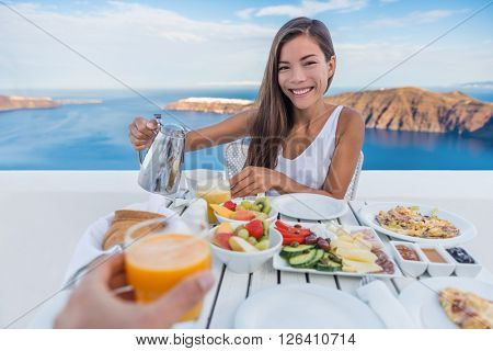 Couple eating breakfast. Smiling tourist woman drinking coffee and man drinking orange juice on terrace resort outdoor. Healthy and delicious food served for breakfast.  Santorini, Greece.