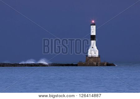 Lake Erie waves splash and spray in moody early morning light at Ashtabula County Ohio's Conneaut West Breakwater Lighthouse. poster