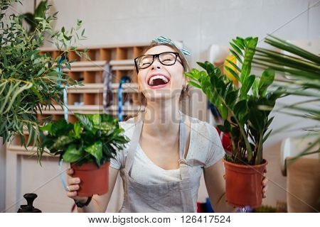 Happy pretty young woman florist holding plants in flowerpots and laughing