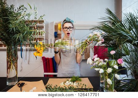 Amazed shoked young woman florist designing bouquet and holding two bunches of flowers