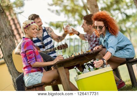Ginger woman takes out cold beer from green picnic handheld refrigerator
