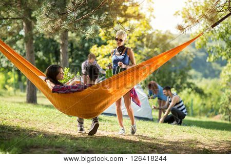 Friend from camp brings beer bootless for couple in love in hammock in nature