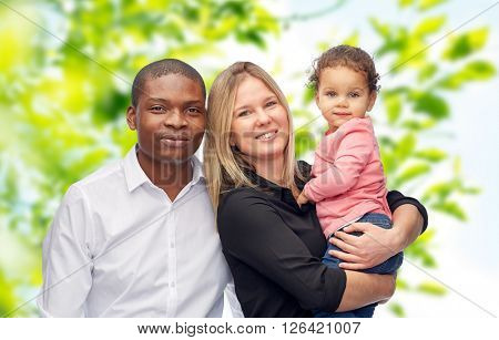 family, children, race and nationality concept - happy multiracial mother, father and little child over green natural background
