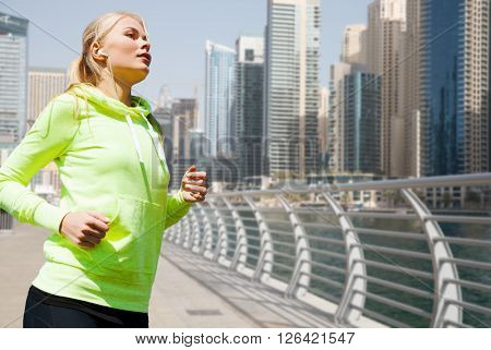 fitness, sport, people and healthy lifestyle concept - young woman with earphones jogging over dubai city street or waterfront background