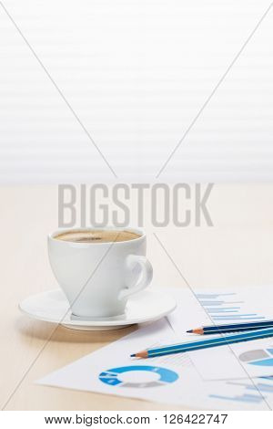 Office workplace with coffee cup and charts on wooden desk table in front of window with blinds