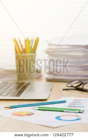 Office workplace with laptop, reports and pencils on wooden desk table. View with copy space