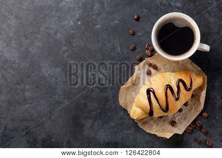 Fresh homemade croissant with chocolate and coffee on stone table. Top view with copy space