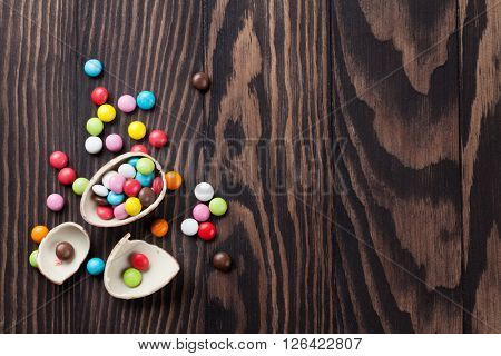 Colorful candies and chocolate egg on wooden background. Top view with copy space