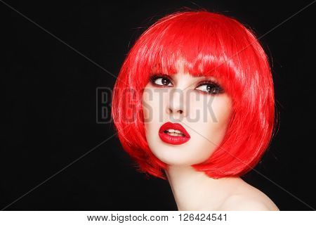 Portrait of young beautiful sexy girl with stylish make-up and fancy bob style red wig
