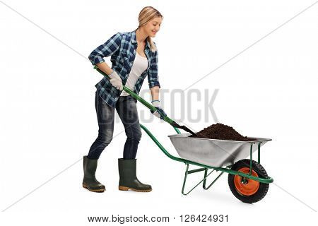 Young blond woman shoveling dirt out of a wheelbarrow isolated on white background