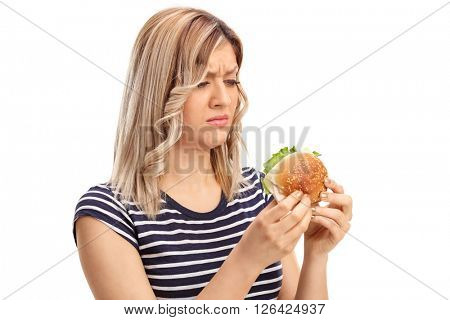 Sad woman holding a tasty looking sandwich and thinking isolated on white background
