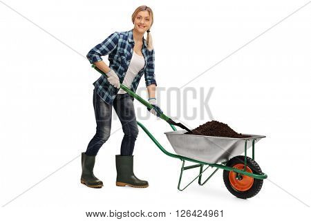 Young woman unloading dirt from a wheelbarrow and looking at the camera isolated on white background