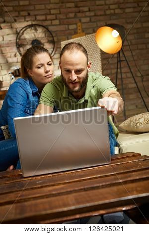 Young loving couple using laptop computer at home.