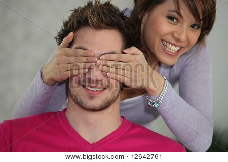 Young woman hiding eyes of a man