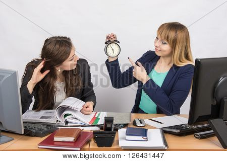 Girl Shows A Colleague In The Office The Rest Of The Working Time On The Clock