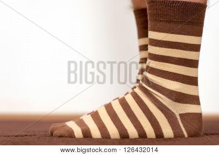 Wearing comfortable striped socks at home, human feet