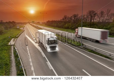 Two trucks driving towards the sun in blurred motion on the freeway at beautiful sunset. Transport scene on the motorway near Belgrade Serbia.