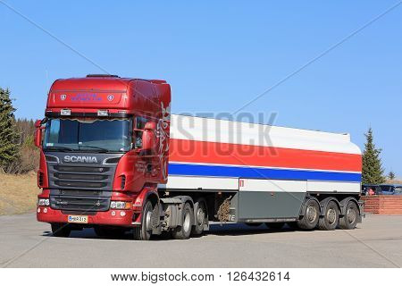 SALO FINLAND - APRIL 16 2016: Red Scania R580 Semi tank truck stops at the asphalt yard of a truck stop in South of Finland on a sunny day with blue sky.