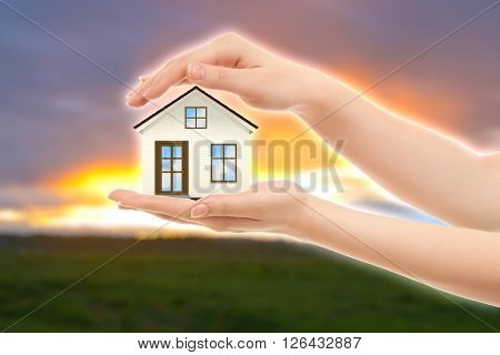 Picture of woman's hands holding a beautiful house against nature
