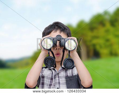 Young boy watching bird by binocular in forest
