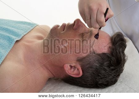 Face Of Laying Man With Cream Mask, Hands Of Beautician