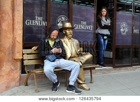 VELIKO TARNOVO, BULGARIA - MARCH 19, 2016: An unidentified Caucasian man and a girl next to the golden sitting statue of a gentleman