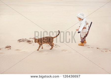 Concept of travel and fascinating adventures. hild in suit of treasures seeker like Indiana Jones in the desert whit wild cat similar to tiger