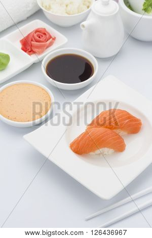 Salmon Sushi Nigiri With Ginger Wasabi And Soy Sauce On A White Plate