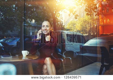 View through the window of a business woman talking on mobile phone while is waiting for her order in cafe young hipster girl calling with cell telephone while sitting in contemporary coffee shop
