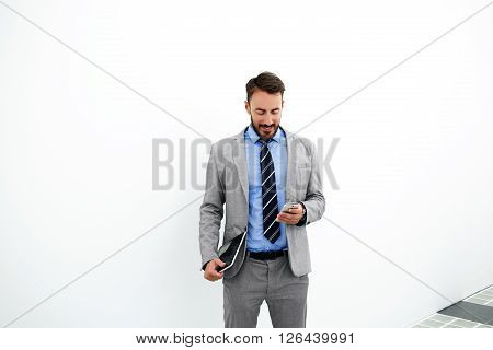 Young man successful employee of brokerage firm with portable touch pad in hand is reading good news from his client while is standing near copy space for your advertising text message or content