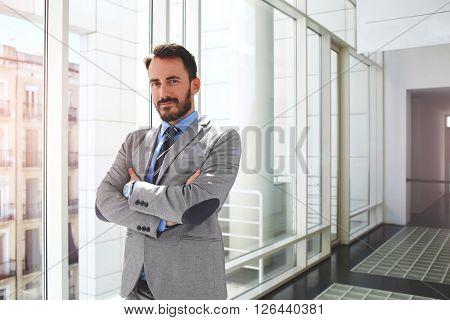 Young handsome man successful lawyer dressed in formal wear is standing in modern interior near office window. Proud male banker in suit is posing for camera in corridor company during break at job