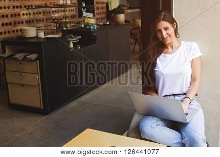 Gorgeous female freelancer using net-book for distance job while sitting in modern coffee shopyoung hipster girl looking at you while working on her laptop computer and relaxing during lunch break