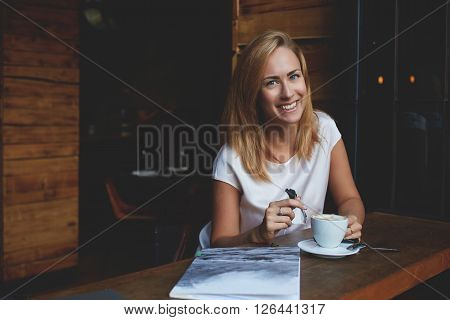 Attractive happy hipster girl with good mood is posing while sitting alone in modern coffee shop interior cheerful Caucasian woman with beautiful smile enjoying her recreation time in cozy cafe bar poster