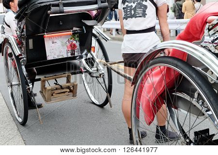 TOKYO, JAPAN - MARCH 30 2016: Tourists take a rickshaw ride to explore the city around Senso-ji Temple in Asakusa on March 30 2016. The Rickshaws are a popular way to tour the city.