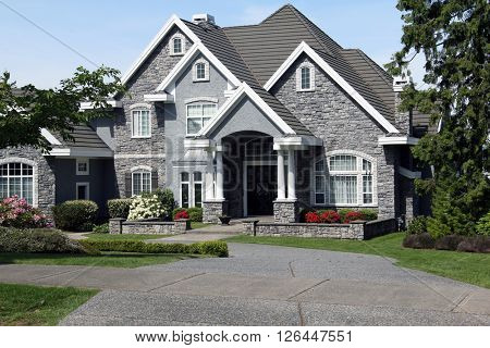 Beautiful luxury mansion with manicured front lawn.