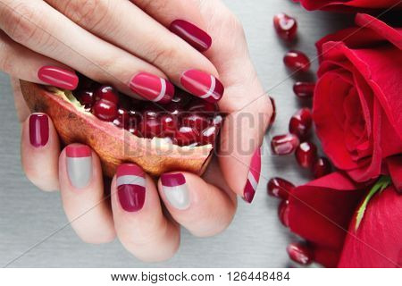 Skin care of a beauty female hands with grey pink and red asymmetry nail art manicure. And pockmarked grey background with red roses and pomegranat's seeds