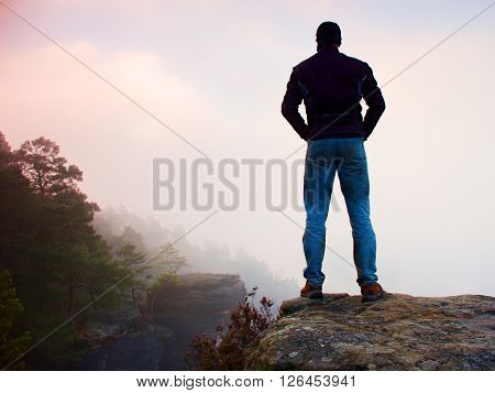 Tourist In Black Jacket And Blue Jeans On The Sharp Peak Of Rock Above The Misty And Foggy Morning V