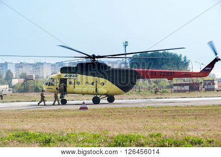 Tyumen, Russia - August 11, 2012: On a visit at UTair airshow in Plehanovo heliport. Rescuers load into helicopter MI-8