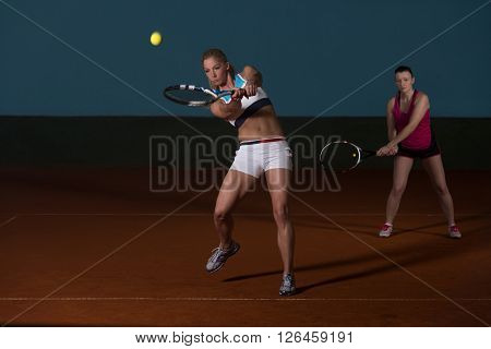 Two Sporty Female Tennis Players Enjoying A Game