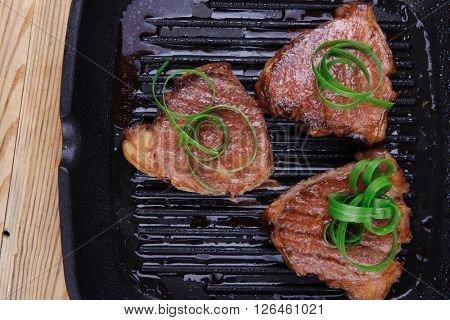 grilled beef fillet strips on grill teflon black plate over wood