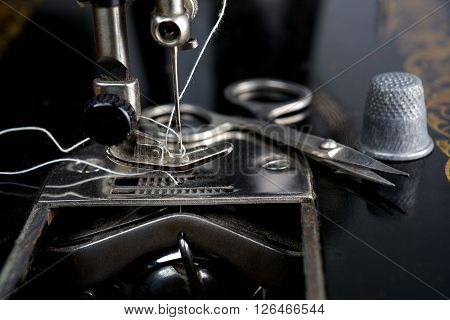 Vintage sewing machine with old sewing utensils