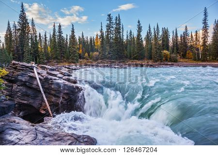 Scenic and powerful Athabasca Falls. Sunset  illuminates the surrounding mountains. Canada, Jasper National Park