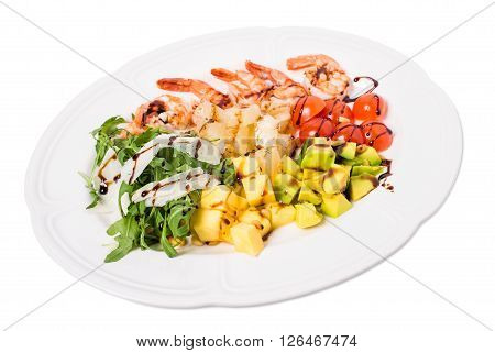 Jumbo shrimp salad with avocado and mango topped with pine nuts and parmesan cheese. Isolated on a white background.